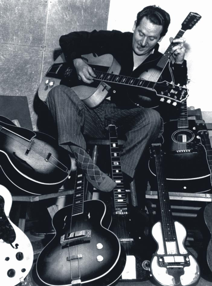 Les Paul Sitting With Guitars Portrait